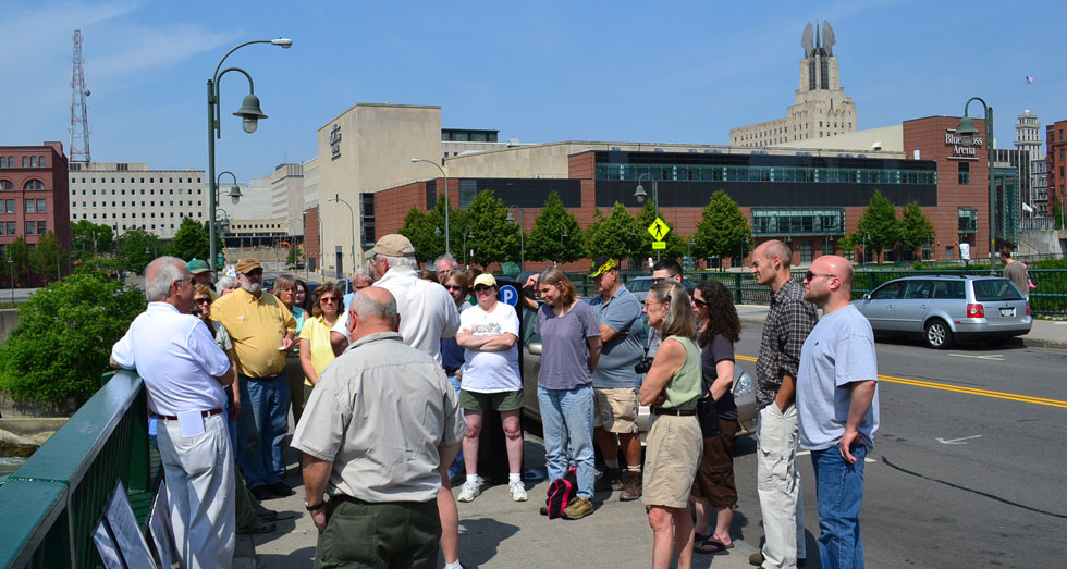 Members of Reconnect Rochester speaking to MCC faculty on the Court Street bridge about Rochester's transit future.