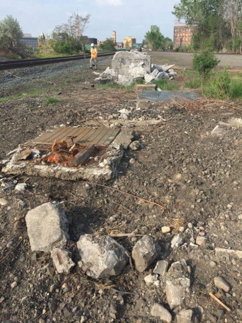 Pit with water line and valve in foreground. Background is a concrete block at the end of former tracks. 5-22-15 [PHOTO: NYSDOT]
