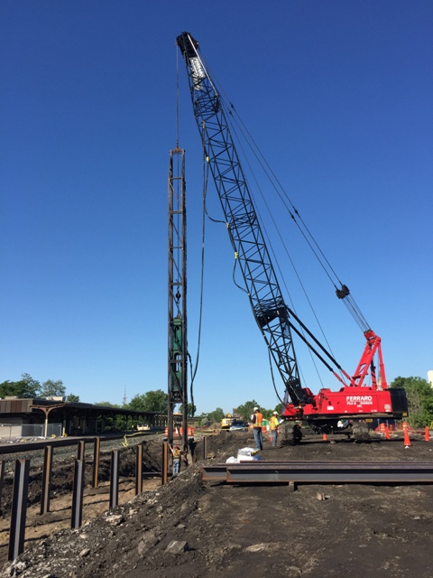 Driving piles for new platform between the rails east of the existing station. 6-4-15 [PHOTO: NYSDOT]