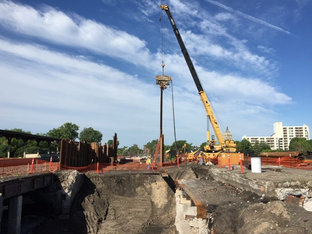 Sheeting and shoring is being installed between railroad tracks in preparation to excavate, drive piles and form the platform. 6-23-15 [PHOTO: NYSDOT]