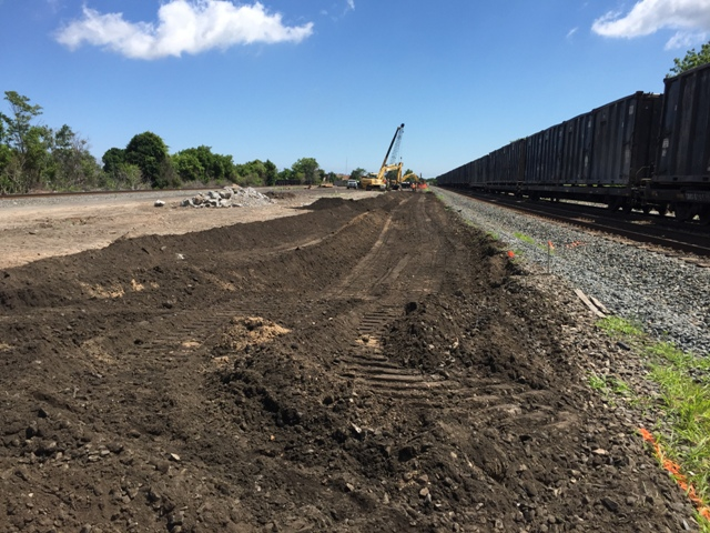Undercut and rough grading with bulldozer and excavator in preparation for the new rail bed. Concrete pile is from the demolished rail terminus blocks. Picture is taken from the far west end of the project facing east. 6-26-15 [PHOTO: NYSDOT]